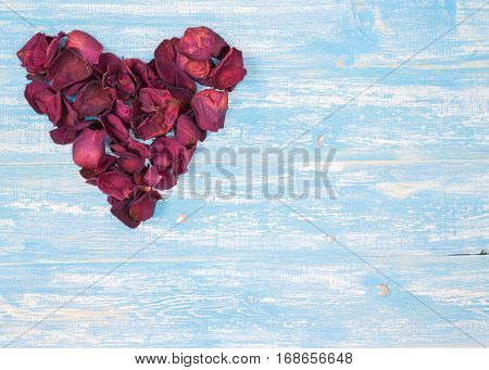 Rose petals in a heart shape on the vintage wooden table. The concept of love heart.