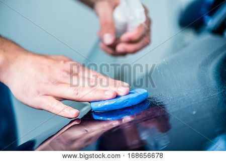 Close-up of male hands waxing the surface of a blue car at auto wash