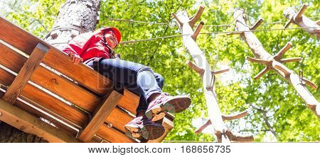 Girl sitting on platform in high rope course resting