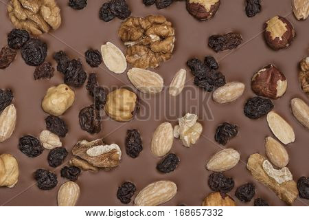 Milk chocolate background with nuts and raisins