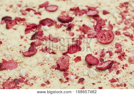 White chocolate background with berries and nougat