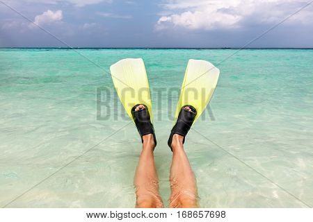 Ready to go snorkeling in the ocean. Fins on legs in clear water, Maldives.