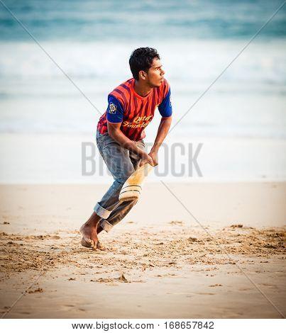 GALLE, SRI LANKA - JAN 14, 2015: Srilankan boy playing cricket. o the beach. Cricket is the most popular game in Sri Lanka.