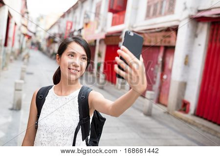 Woman using cellphone to take selfie in Macao city