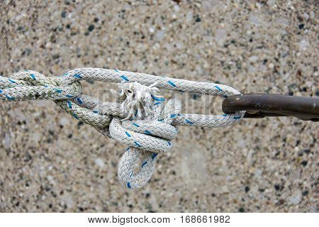 frayed rope with tight knot and rusty hook