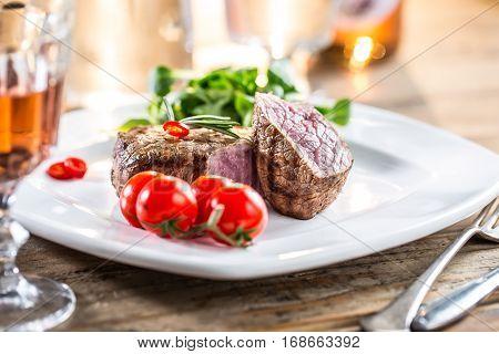 Beef Steak. Juicy beef steak. Gourmet steak with vegetables and glass of rose wine on wooden table.