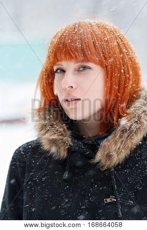 Winter portrait of a cute red-haired girl with a defiant look in a black jacket with fur during a snowstorm red-haired woman stands in the street during a heavy snowfall look at the camera