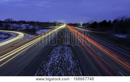Multi-lane highway during rush hour winter commute light trails showing motion of cars