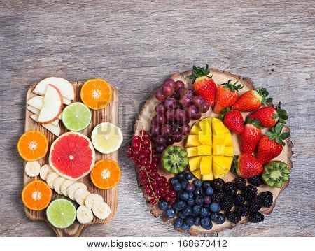 Raw fruit and berries platter mango kiwis strawberries blueberries, blackberries, red currants, grapes, top view, copy space for text