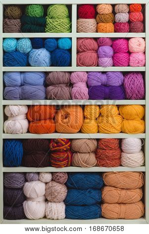 Colorful Balls Of Wool On Shelves. Variety of knitting yarns. Different Yarn balls in multiple colors. Yarn Storage.