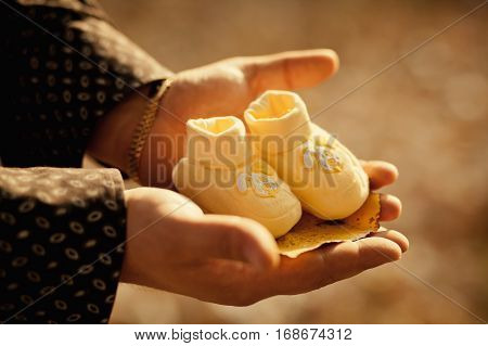 father holding baby booties close up. Family