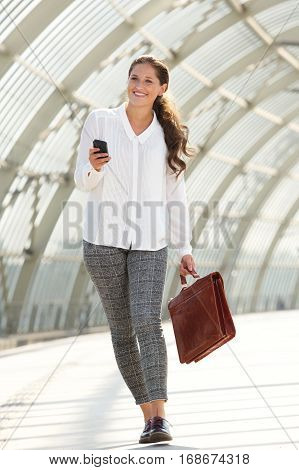 Happy Business Woman Walking With Briefcase And Cellphone