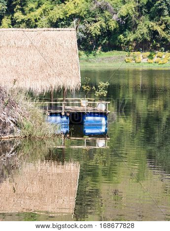 Wooden pavilion raft is floating on the clear water of the small lake in the national park.