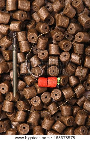 Fishing bait with hook on brown pre-drilled halibut pellets for carp fishing background