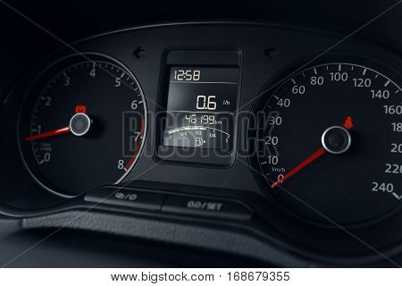 Modern car dashboard display with analog speedometer and odometer close up