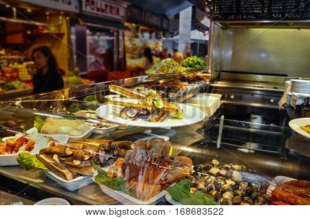 BARCELONA SPAIN - MAY 2016: Fried Gould's razor shell or Canyut navaja in olive oil and pesto. Shrimps bamboo jack knife clams and mussels on ice in glass case of cafe at Mercat de Boqueria market