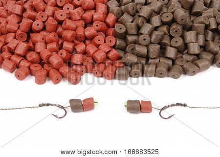 Fishing bait with hook and brown with red pre-drilled halibut pellets for carp fishing isolated on white background with soft shadow