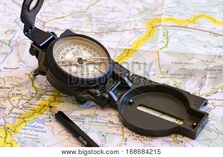 still life with a compass and over a map. the yellow line indicate the path. travel. journey. direction.
