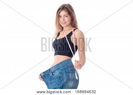 Slim young girl wore jeans to the large size isolated on white background
