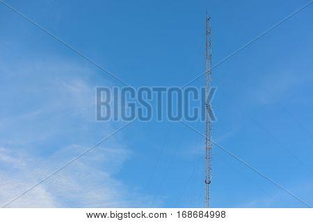 Phone antenna with blue sky background, telecommunication.