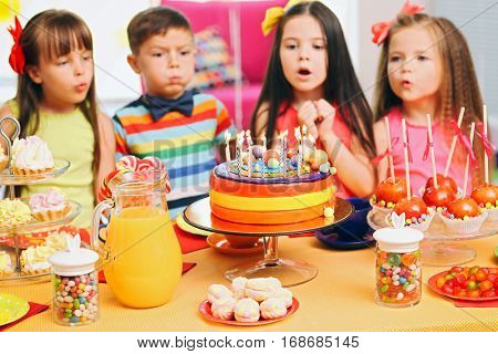 Children blowing candles on tasty cake at birthday party