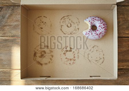 Donut with bite taken out lying in carton box
