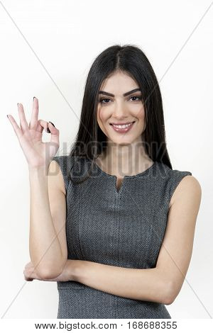 Young business woman standing and giving ok hand sign. She is looking at the camera and smiling.