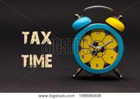 Concept,alarm Clock With Tax Time Phrase Written On Black Background