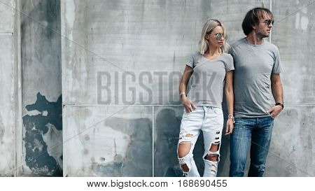 Two hipster models man and woman wearing blank gray t-shirt, jeans and sunglasses posing against rough concrete wall in the city street, front tshirt mockup for couple, urban style