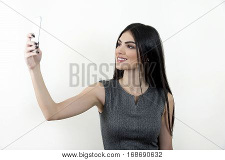Young business woman using her smart phone to shoot a selfie and smiling.