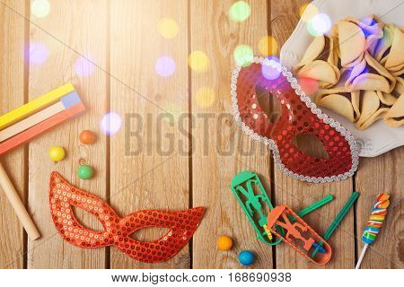 Purim holiday concept celebration with hamantaschen cookies and mask on wooden background. Top view from above
