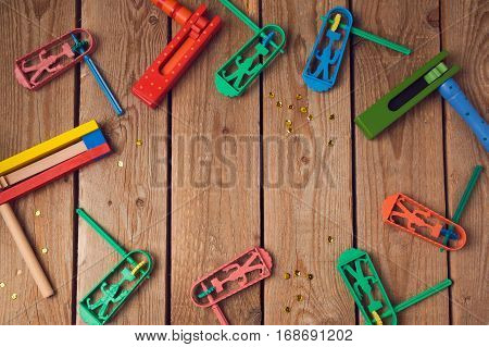 Purim holiday concept with noisemakers on wooden background. Top view from above