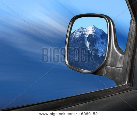 Rear view mirror reflecting beautiful winter mountain scenery