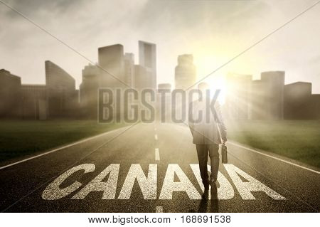 Businessman walking on the road while carrying a briefcase with word of Canada at sunrise