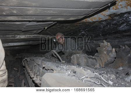 Donetsk Ukraine - August 16 2013: Miner near the coal mining shearer. Mine is named Chelyuskintsev