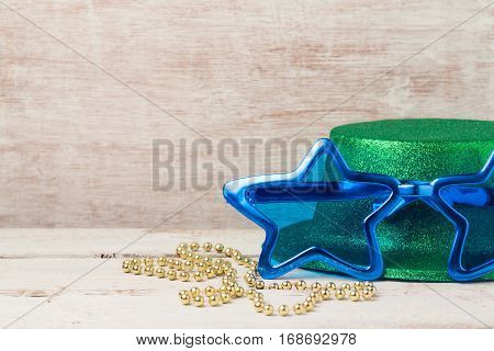 Mardi gras carnival glasses with star shape and hat for party on wooden background