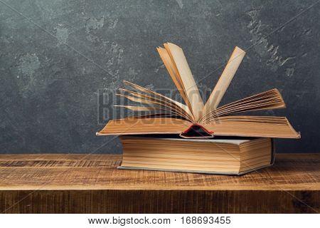 Vintage old books on wooden table over blackboard background. Education concept