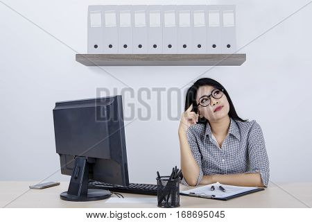 Portrait of female entrepreneur daydreaming in the office while sitting in front of computer