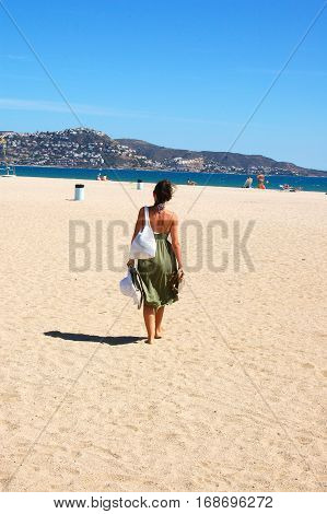 Rear view of a young woman strolling on the beach alone.