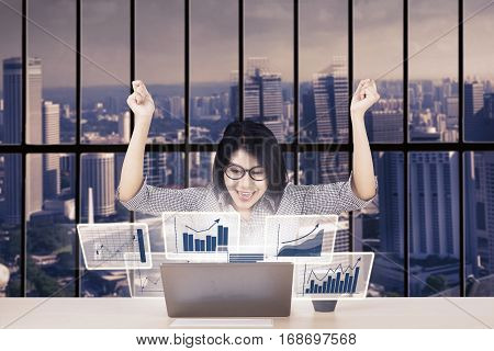 Picture of happy female worker celebrates her success while looking at virtual financial statistics on the laptop screen in the office