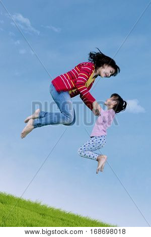 Little girl and young mother leaping on the air together while playing on the meadow