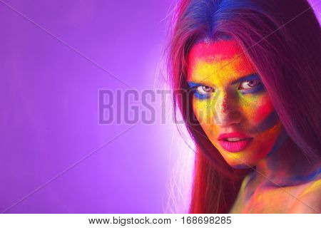 Portrait of attractive young woman with bright facial body-art on purple background