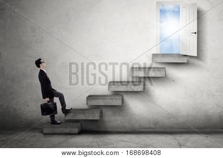 Young businessman carrying a briefcase and walking on the stairs toward an opportunity door with bright sunlight