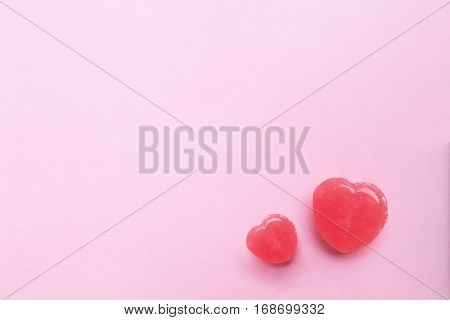 two Pink Valentine's day heart shape candy on empty pastel pink paper background. Love Concept. top view. Minimalism colorful hipster style.