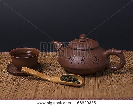 Chinese brown teapot, teacups and wooden spoon of tea