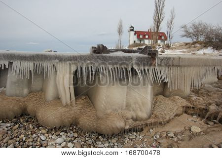 An ice covered breakwater and Point Betsie Light in Michigan