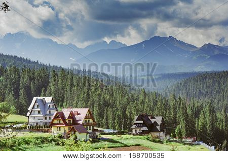 Guest house in the traditional mountain style and mountain landscape. View of cottage from wooden. Tatra mountains. Poland. Copy space. Summer trave poster