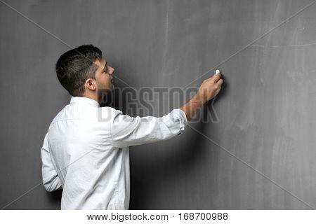 Handsome young teacher writing on blackboard