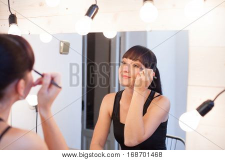 beautiful girl makes herself the makeup takes care of face