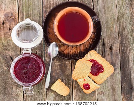 Tea drinking with red berries jam and cookies flat lay. The ceramic cup with tea costs on a table from old boards the jar of jam and pieces of cookies smeared with jam nearby
